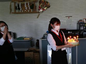 誕生日ケーキを運ぶ小泉さん