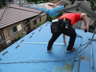 屋根の寸法をメジャーで測る白石支店長